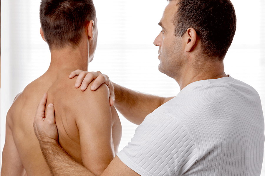 Physical therapist adjusting a man's kyphosis