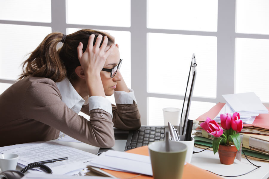 """Female office worker slouched at her desk, wondering """"What is posture?"""""""
