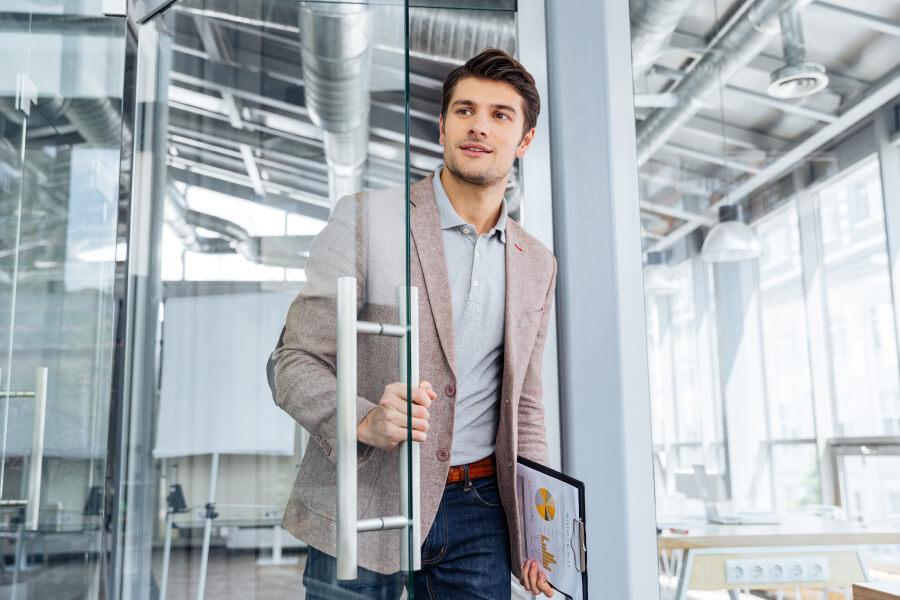 Man entering office through glass door