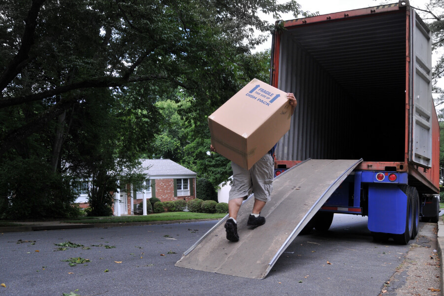 Mover carrying a heavy box on his back