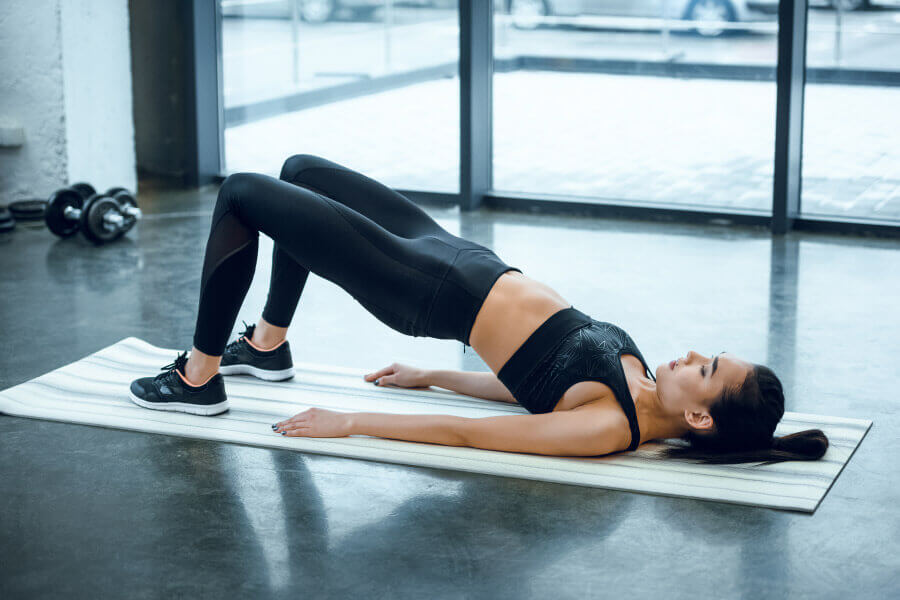 Woman in a hip bridge pose - one of the more effective lordosis exercises