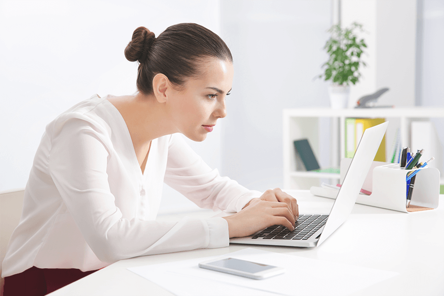 Woman with poor posture working on her laptop
