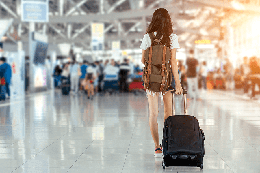 Woman walking through an airport with a luggage bag