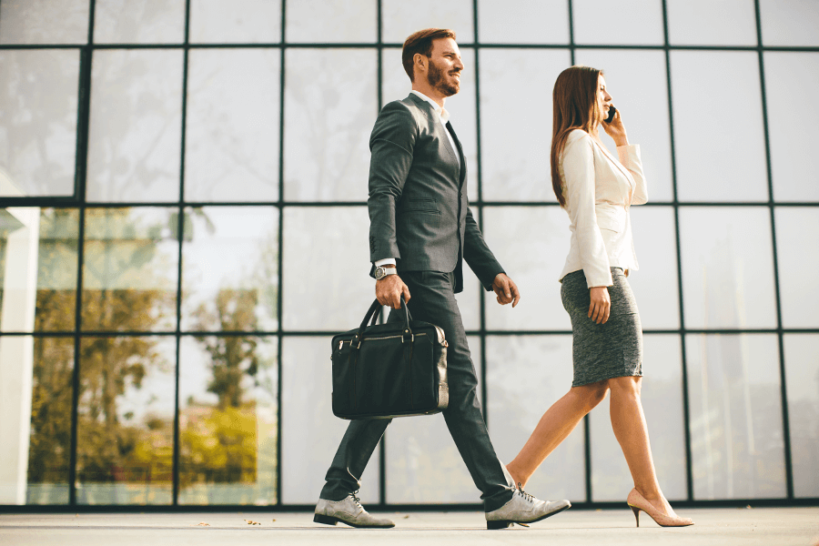 Man and woman with good posture walking in an office building