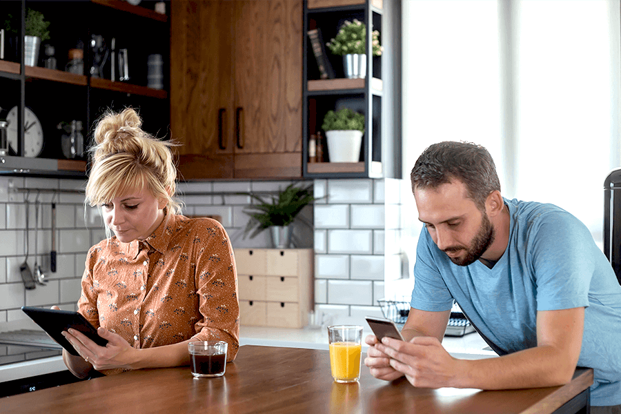 Man and woman in their kitchen looking down at their smartphones