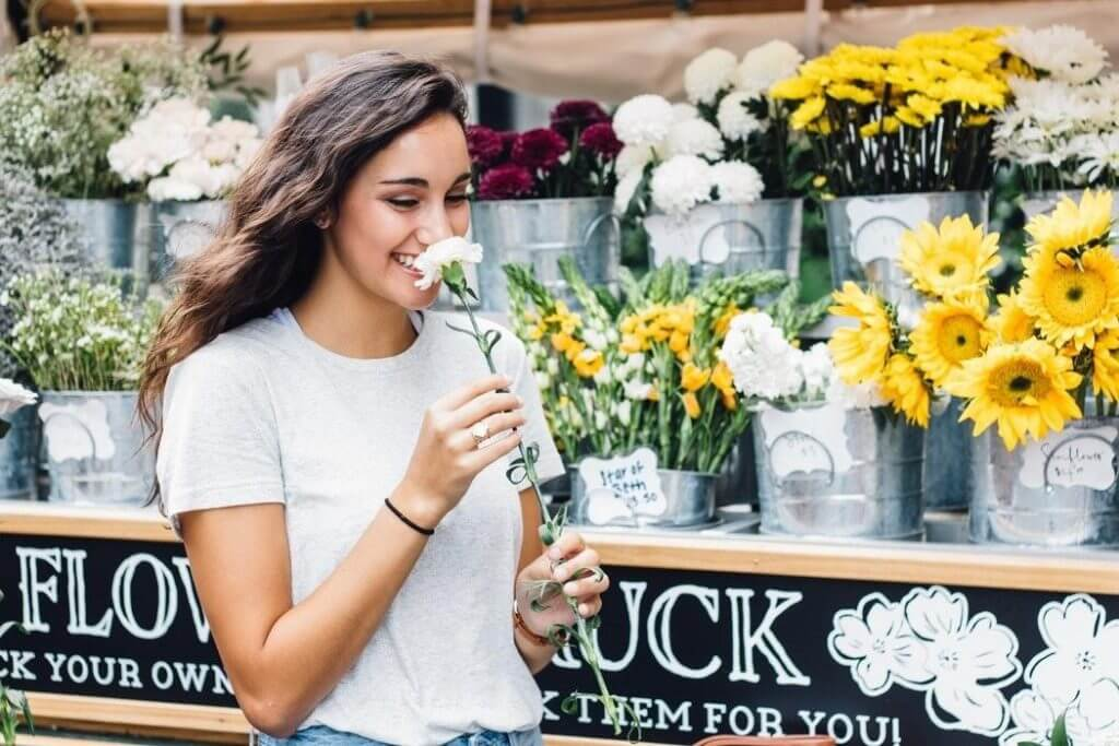 Woman walking by a flower truck smiling and smelling a flower