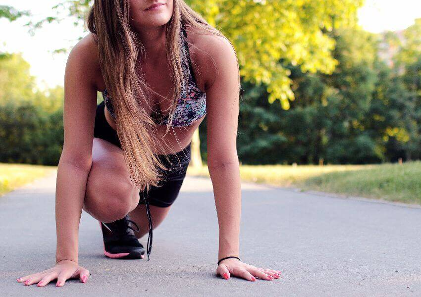 Woman stretching outside before exercising to improve her posture