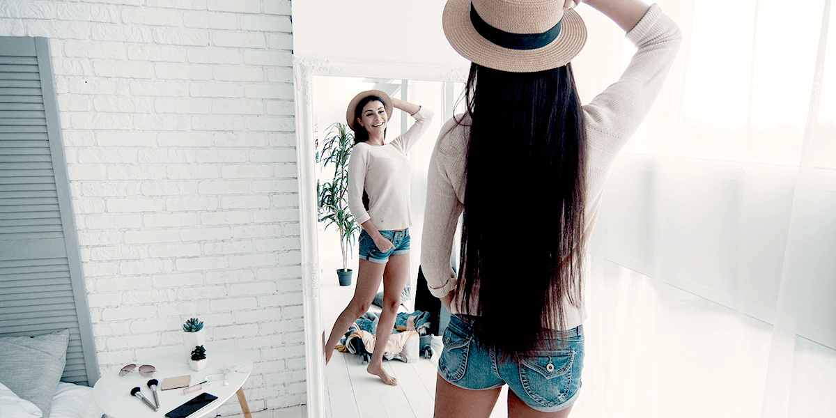 Woman posing and smiling to herself in a mirror